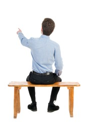 back view of business man sitting on chair and pointing.  businessman watching. Rear view people collection.   Isolated over white background. Businessman resting on a wooden bench