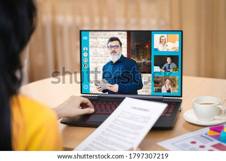 Back view of business woman discussing company plan in video conference – Multiethnic business team using laptop for online meeting in video call – Group of people remote working using web app