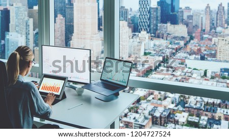 Back view of business woman sitting at panoramic skyscraper office desktop front PC computer with financial graphs and statistics on monitor.Analysis of digital market and investment in block chain