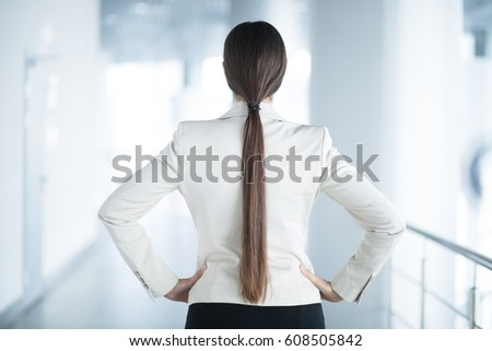 Back View of Business Woman Standing in Hall