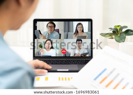 Back view of business woman talking and discussion in video conference. Asian team using laptop and tablet online meeting in video call.Working from home, Working remotely and Self-isolation.