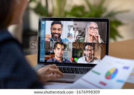 Photo of  Back view of business woman talking to her colleagues about plan in video conference. Multiethnic business team using laptop for a online meeting in video call. Group of people smart working from home