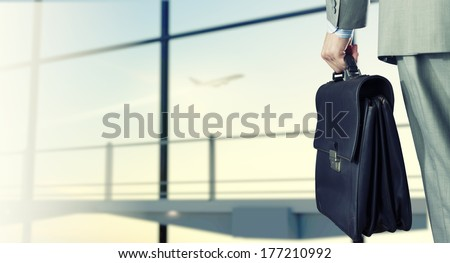 Back view of businessman at airport with suitcase in hand #177210992