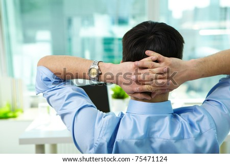 Back view of businessman having break in office