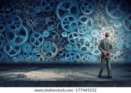 Back view of businessman looking at mechanism of cogwheels #177469232