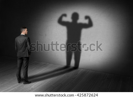 Back view of businessman looks to his shadow with strong his display in future. Believe in yourself. Success and development. Setting and achieving goals. The look into the future.