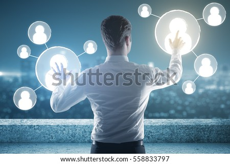 Back view of businessman on rooftop managing people icons. HR concept