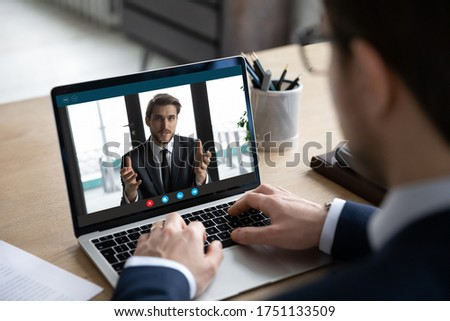 Back view of businessman sit at desk have video call on laptop with male business partner, man employee or boss engaged in webcam conference, brainstorm have team meeting with colleague or client