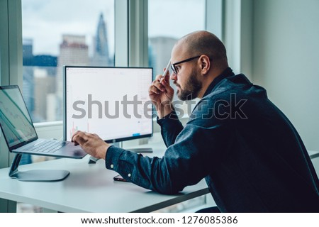 Back view of businessman sitting at office desktop front PC laptop computers with financial graphs and statistics on monitor.Making research, analysis of digital market and investment in block chain #1276085386