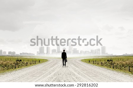 Back view of businessman standing at crossroads and making choice
