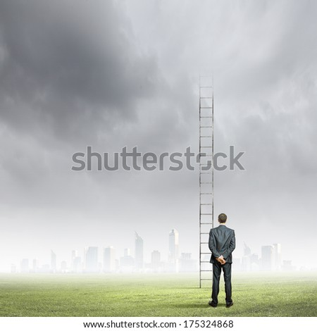 Back view of businessman standing near long ladder to sky