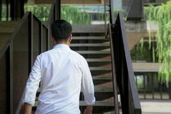 Back view of businessman walking up staircase. Back to office or climbing up the corporate ladder concept,