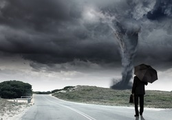Back view of businessman with umbrella and suitcase facing tornado