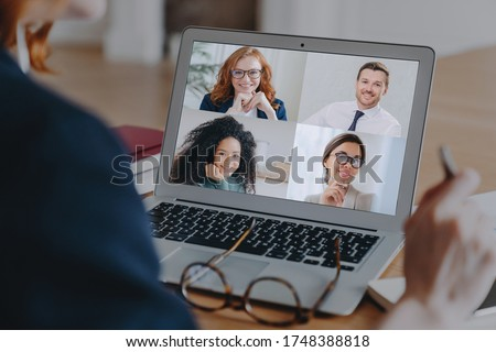 Back view of businesswoman engaged in team Webcam conference on laptop, have online briefing or consultation from home, woman worker speak talk on group video call with colleagues