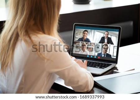 Photo of  Back view of businesswoman speak using Webcam conference on laptop with diverse colleagues, female employee talk on video call with multiracial coworkers engaged in online briefing from home