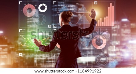 Back view of businesswoman working with virtual panel and night city at background #1184991922