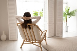 Back view of calm young woman sit rest in cozy modern chair in living room stretch breathe fresh air. Happy female renter relax in armchair at home look in window think or visualize enjoy weekend.