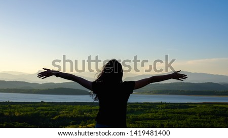 Back view of carefree happy woman enjoying scenic view of lake on sunset. Freedom and life enjoyment concept. #1419481400