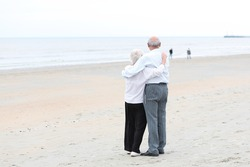 Back view of caring couple of two seniors, a man and his wife, standing together on a sandy peaceful beach looking at the ocean