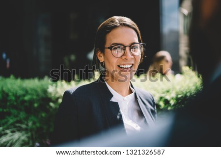 Back view of cheerful excited female entrepreneur in optical spectacles for provide eyes protection laughing from colleague joke during break on publicity area, happy woman smiling outdoors