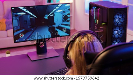 Back view of cheerful young girl playing shooter games sitting on gaming chair. Room with colorful neon lights.