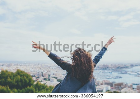Back view of cheerful young woman with hands up. Freedom concept.