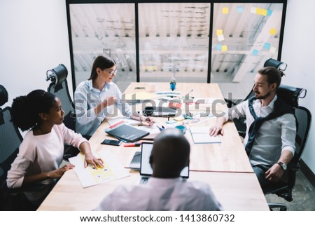 Back view of clever financial experts dressed in formal apparel sitting in office and searching solutions for productive strategy, diverse male and female colleagues listening boss of company #1413860732