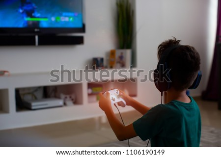 Back view of concentrated young gamer playing game. gaming game play tv fun gamer gamepad guy controller video console playing player holding hobby playful enjoyment view concept.