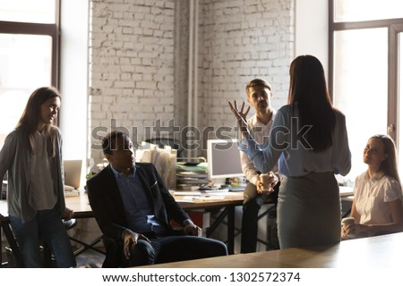 Back view of confident businesswoman standing in front of colleagues, gesturing talking about business ideas or projects, female team leader hold briefing or informational meeting with employees Photo stock ©