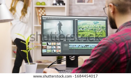 Back view of creative content creator working from home on a multmedia project. Girlfriend in the background. Foto stock ©