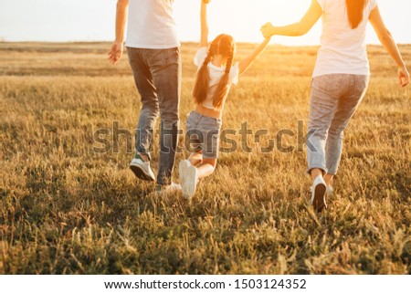 Back view of crop parents carrying daughter over grass while walking and having fun in meadow in evening #1503124352