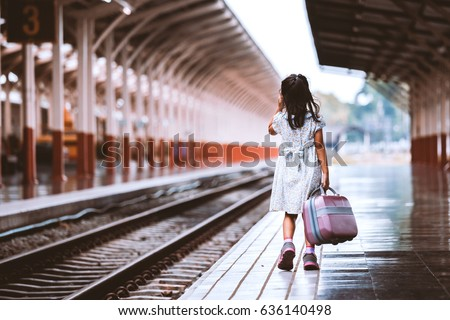 Back view of cute asian little girl holding suitcase and walking on a railway station in vintage retro style