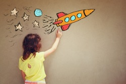 back view of cute kid (girl) imagine space rocket with set of infographics over textured wall background