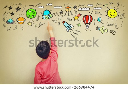 back view of cute kid imagine space travel with set of infographics over textured wall background