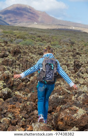 Back view of cute young girl with backpack have trip in the mountains. Vertical view