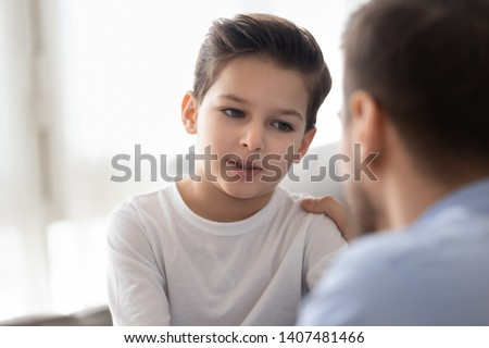 Back view of dad sit on couch with preschooler son talking sharing thoughts or problems, loving father speak have conversation with little boy child, support him showing care and understanding