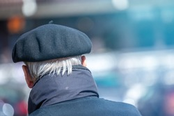 Back view of elderly male with typical french cape beret walking on blurred background of street in Pyrenees, France