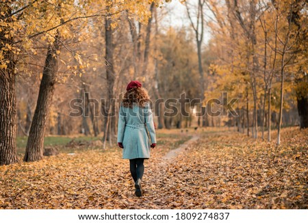 Back view of elegant young woman in gray casual coat in autumn. Cute model walks in the park in golden autumn against background of nature. Autumn walk.