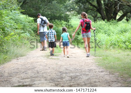 Back view of family on a trekking day in countryside