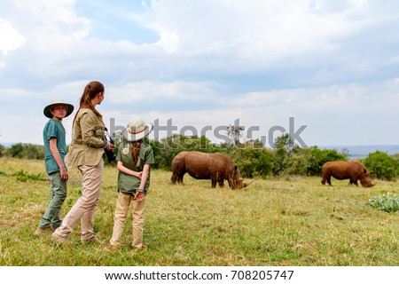 Back view of family on safari walking close to  white rhino #708205747