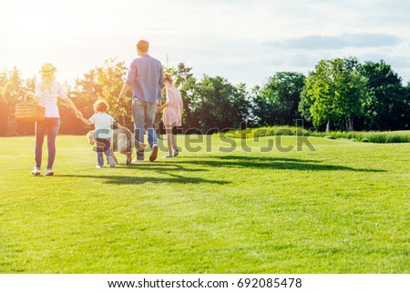 back view of family with pet walking on green meadow in park #692085478