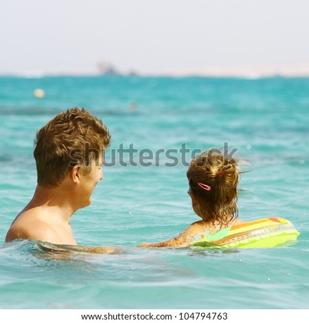 Back view of father and daughter looking to ocean
