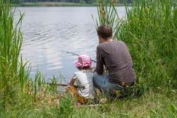 Back view of father and daughter sitting on grass and fishing on the lake