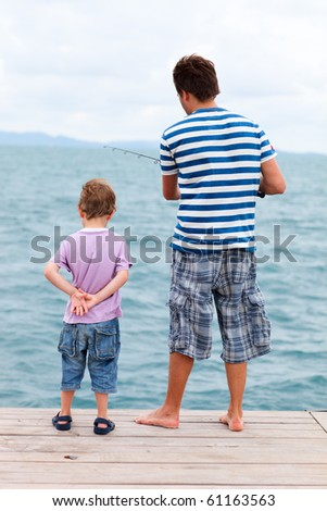 Back view of father and son fishing from pier