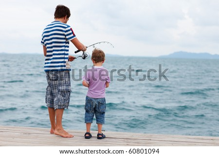 Back view of father and son fishing on summer day