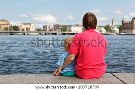 back view of father and son sitting on pier