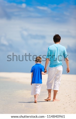 Back view of father and son walking on a tropical beach - stock photo