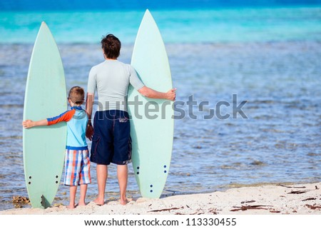 Back view of father and son with surfboards at beach