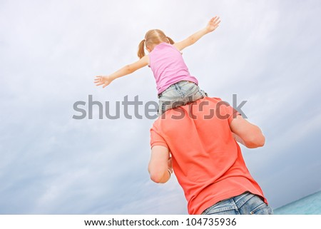 Back view of father carrying his little daughter on shoulders