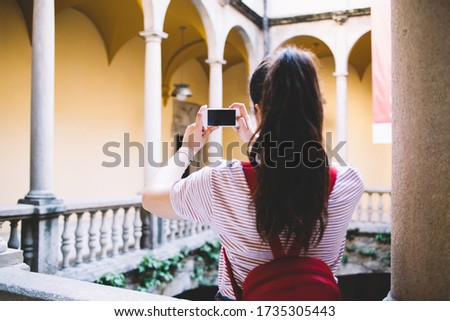 Photo of Back view of female blogger holding mobile phone taking picture of architecture building during trip vacation, woman 20s using smartphone and app for shooting video and share content with followers
